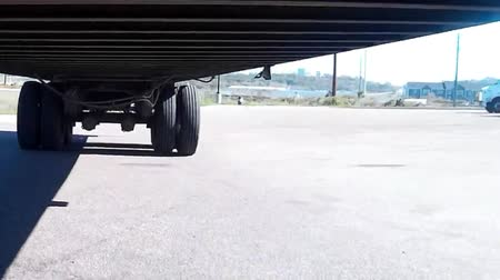 truck stop : Camera mounted under a semi truck trailer pointing back at the rear axles whilst in motion.