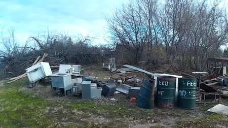 apiary : Pile of junk left outside on a derelict piece of farmland. Barrels, units, fridge, freezers, furniture.