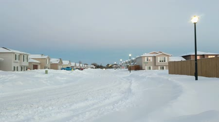 festividades : Residential street covered in snow at Christmas Time, just before dusk. Street lights are illuminated. Headlights of cars can be seen in the distance, which gives the video some movement. Stock Footage