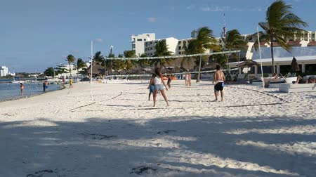 volleyball : Group of young people play beach volleyball. Girl falls over backwards.
