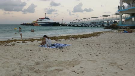 tyrkysový : Establishing shot. Young girl sitting on a beach towl, on sandy beach near the pier. People are in the swimming and playing in the sea. There is a large tourist boat at the end of the pier. Dostupné videozáznamy