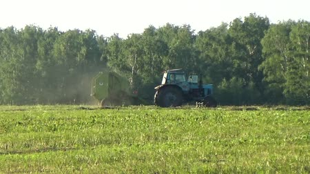 hay fields : Tractor collecting grass clippings