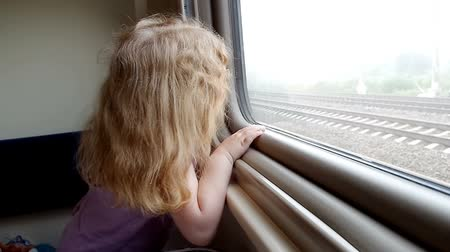 Beautiful little girl stares in the train window and laughing while travelling raylway Stok Video