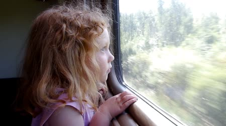 Beautiful little girl looking through the train window while traveling railway Stok Video