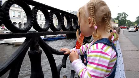 Charm little girl standing at the river embankment sucking lollipop Stok Video