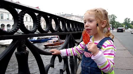 Charm little girl at river embankment sucking lollipop and looking at boats Stok Video