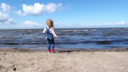 Beautiful little girl on a sea side plays with surf waves