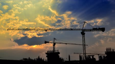 montáž : time lapse sunset and silhouette crane crane working in construction site