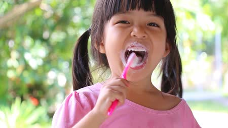 little : Cute Asian Girl Brushing Teeth (With Toothpaste) Stock Footage