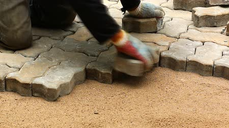 cement floor : worker installing old cobblestone block for build floor ground