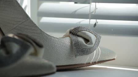 high heeled sandals : Close up of a brides wedding shoes displayed on a bed.
