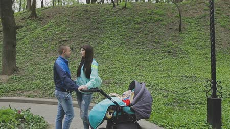 wozek dzieciecy : A married couple is standing with a stroller and talking Wideo