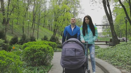 wozek dzieciecy : A married couple walks in a park with a stroller and talks