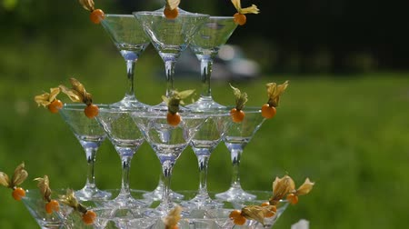 pyramida : The guests hands take glasses with bubbling wine at the party. Glasses are built in the pyramids. No recognizable persons