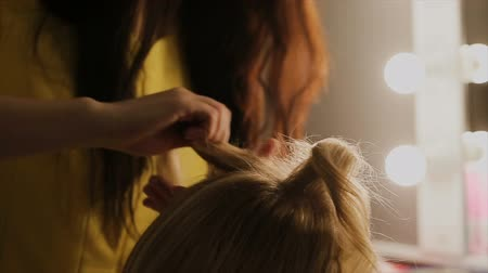 opieka : Hairdresser makes hairstyle blonde girl.