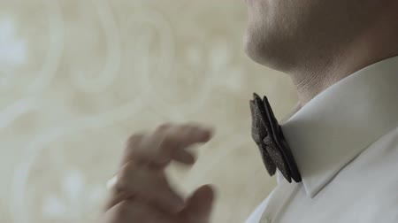 iyi giyimli : A man straightens a butterfly around his neck Stok Video