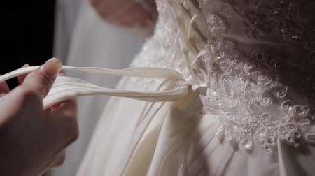 amoroso : Man tying a corset on the brides wedding dress Vídeos