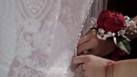 espartilho : Man tying a corset on the brides wedding dress Stock Footage
