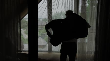 getting ready : Man putting on shirt standing by window at home, slow motion.
