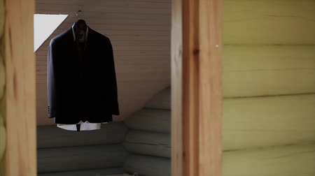 casual wear businessman : A mans jacket hangs on a hanger in the room