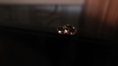 навсегда : Beautiful camera flight to the wedding rings that lie on the corner with a varnished coating