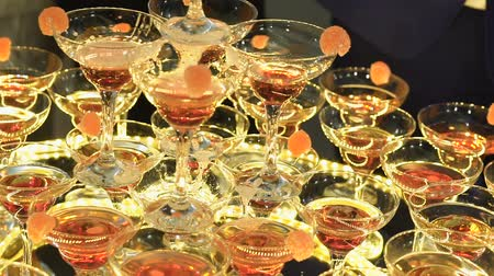 kabarcıklı : A beautiful pyramid of glasses with champagne and pieces of fruit in it Stok Video