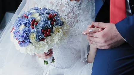 touch : A loving couple holds hands on their wedding day