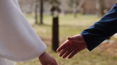 holding : A loving couple holds hands on their wedding day