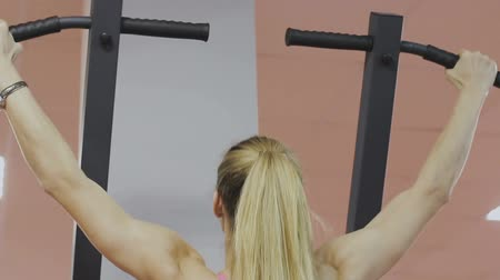 lift ups : Fitness coach of the sports club does pull-ups on the simulator for strengthening the shoulder muscles. A woman does the exercises correctly, pulling up with a straight back