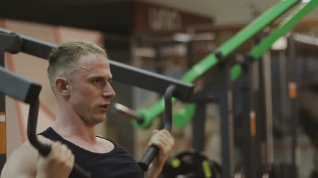 čtyřicet : A muscular man in a black T-shirt is training on a fitness machine in a fitness club.