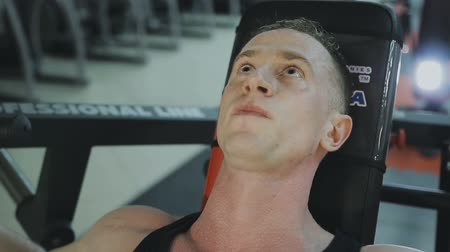 бодибилдинг : A muscular man in a black T-shirt is training on a fitness machine in a fitness club.