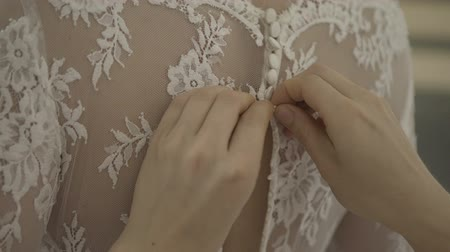 nowożeńcy : Man tying a corset on the brides wedding dress Wideo