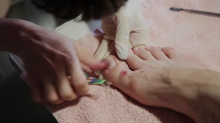 piŁa : Caring about the girl legs pedicure, polish, beautiful lights. Pedicures in the salon. The master cares for the nails and feet of the client, doing the pedicure. Peeling feet pedicure procedure