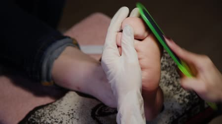 lake : Caring about the girl legs pedicure, polish, beautiful lights. Pedicures in the salon. The master cares for the nails and feet of the client, doing the pedicure. Peeling feet pedicure procedure