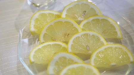 citron : Sliced lemons on a glass plate close up.