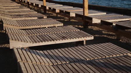 chaise longue : Sun beds on the beach in the evening. Stock Footage