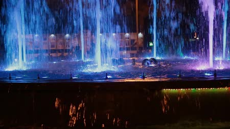 water show : Colorful musical fountain at night, shimmering in different colors.