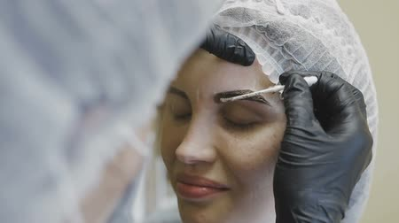 kaşları : The employee of the cosmetology clinic makes manipulations on the coloring of the eyebrows