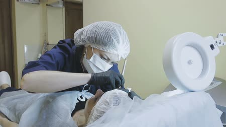 анти : A female employee of a cosmetology clinic makes a microblasting routine to a female patient