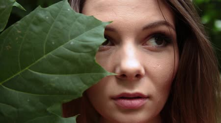 ogród : A girl in a red dress with a large leaf of a green maple on her face. Wideo