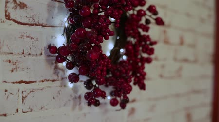 koszorú : A wreath of red berries with light hanging on a white wall.