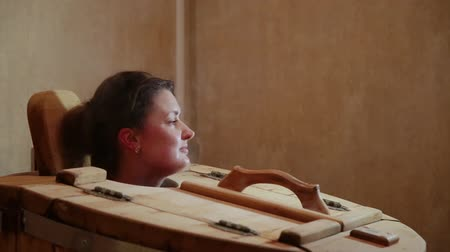 кедр : Female head sticking out of the cedar barrels at a spa salon. Blonde woman passes steam procedure for the recovery of the body in the bath.