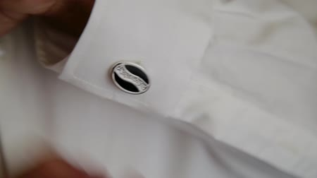 sleeve : Young man puts cufflinks on a white shirt.