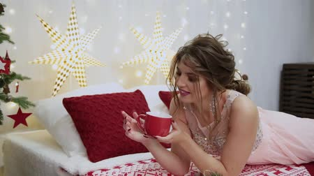 nude : Very beautiful girl drinks tea on the Christmas bed.