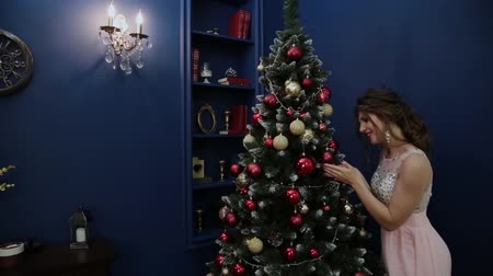 very : Very beautiful girl decorates the Christmas tree.