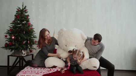 безделушка : Cheerful and beautiful family playing on the bed with a bear in the New Years decor.