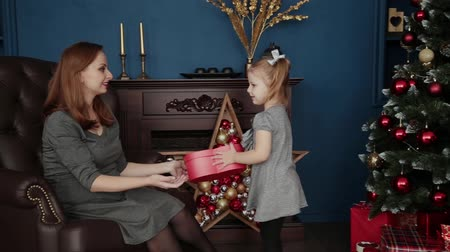 christmas tree decoration : The girl opens a New Years gift with her mother, Christmas 2019.