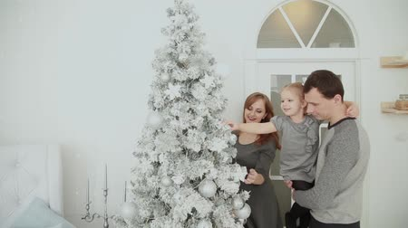 adega : The family is standing near the Christmas tree, laughing talking and touching toys while waiting for Christmas. Vídeos