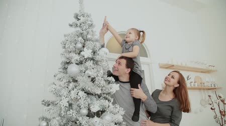 father christmas : The family is standing near the Christmas tree, laughing talking and touching toys while waiting for Christmas. Stock Footage