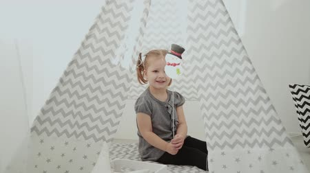 very : Very beautiful and little girl playing in a tepee.